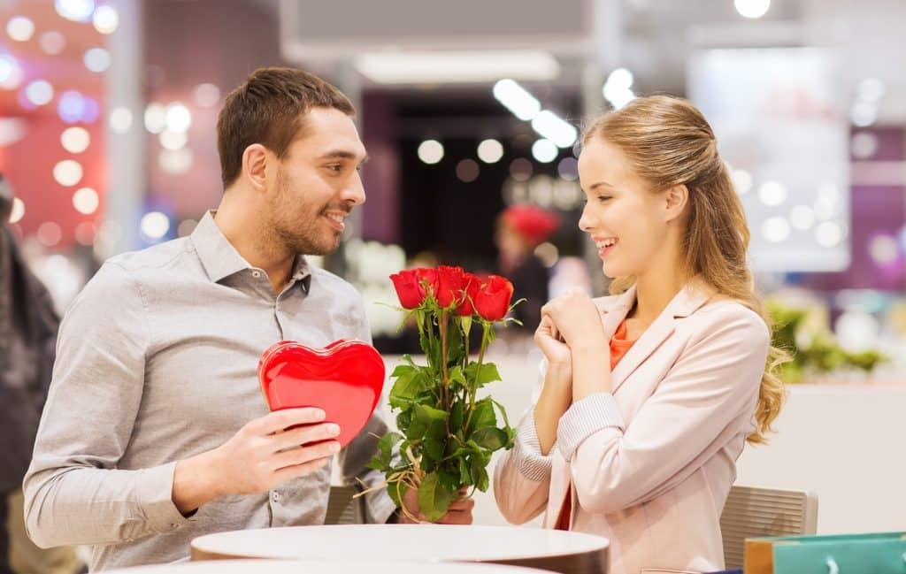 Egy férfi egy csokor rózsát ajándékoz a párjának